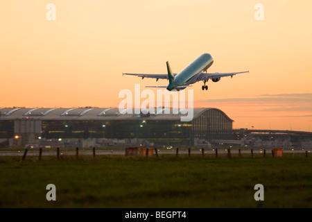 Commercial airplane taking off at London Heathrow Airport with Terminal 5 in the background, UK - Stock Photo