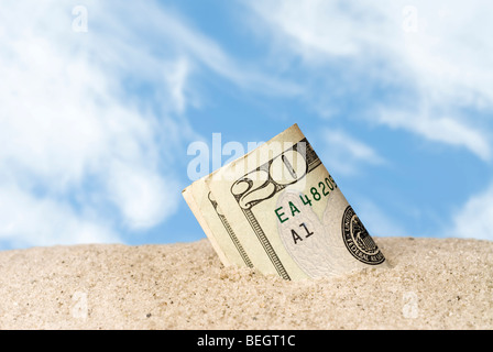 A wad of cash lost and found in the sand at the beach. - Stock Photo