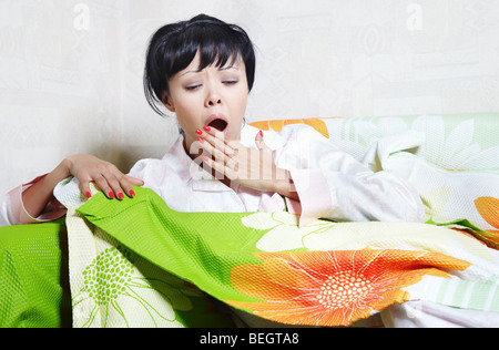 Yawning lady on the bed covered by colorful blanket - Stock Photo