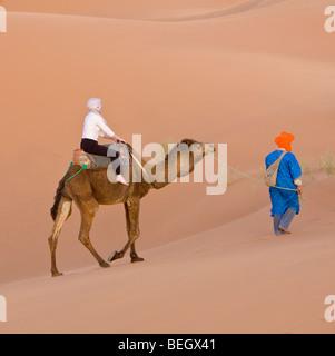 Tourist on a camel ride Merzouga Dunes Sahara Morocco - Stock Photo
