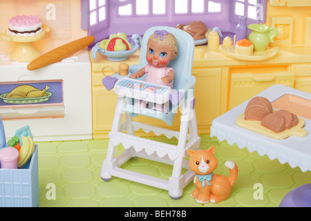 young child doll in a high chair in the kitchen - Stock Photo