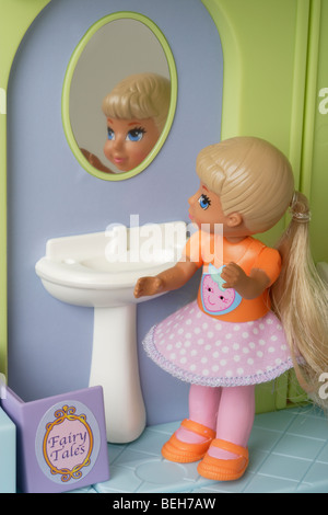 Girl child doll in the bathroom - Stock Photo