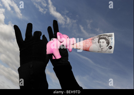 Financial squeeze on savings in piggy bank with low interest rates - Stock Photo