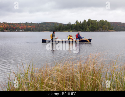 Family with children in a canoe on The Lake of Two Rivers in fall. Algonquin Provincial Park, Ontario, Canada. - Stock Photo