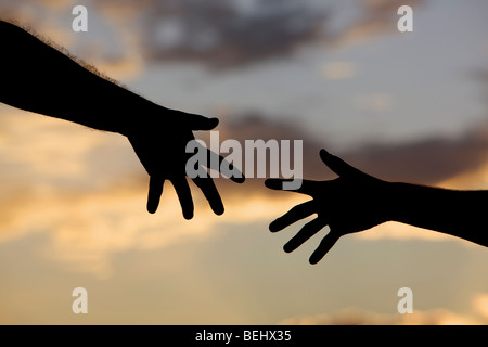 Two people reaching for each other. - Stock Photo