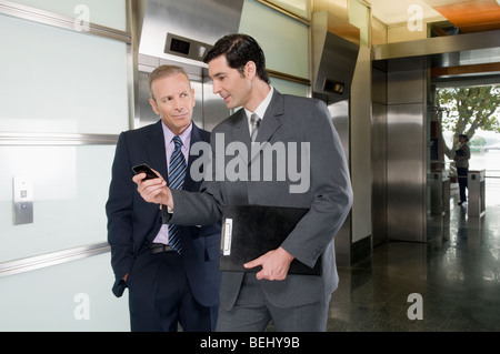 Businessmen walking in a corridor - Stock Photo