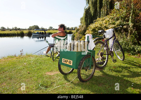 England, Cambridgeshire, Huntingdon, Hartford, pensioner with trailer on bicycle fishing in River Great Ouse - Stock Photo