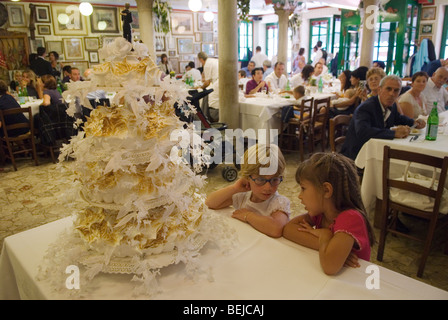 Venice Italy Interior restaurant island of Burano. Children with wedding cake. - Stock Photo
