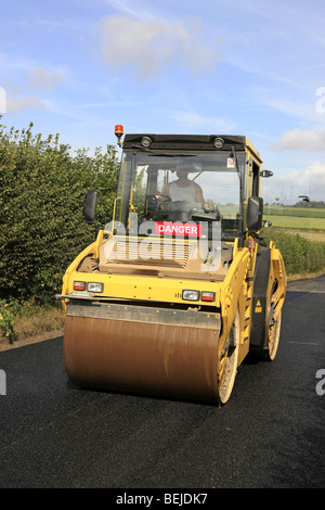 Yellow road roller at work flattening a newly laid tarmac road - Stock Photo