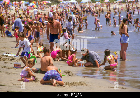 mom dad father mother share play with child boy son girl daughter crowd large group holiday California water build - Stock Photo