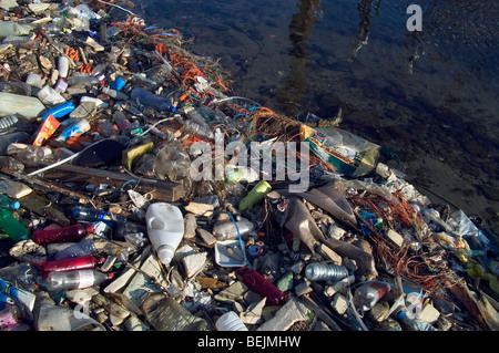 Nondegradable plastic bottles, nylon rubbish and other refuse washed ashore and littering the water - Stock Photo