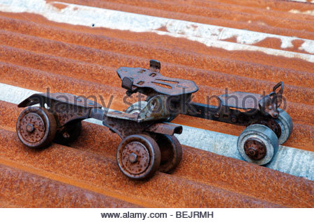 a broken damaged pair of very old rusty roller skates on a rusty corroded corrugated tin sheet - Stock Photo