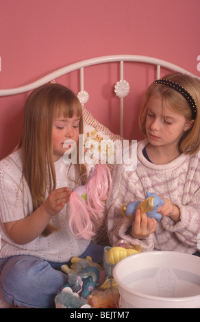 little girl with downs syndrome playing with another little girl - Stock Photo
