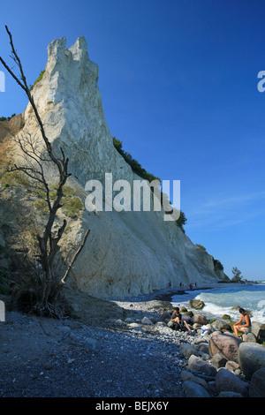 People walking on pebble beach along chalk cliff on the Island Mon, Denmark - Stock Photo