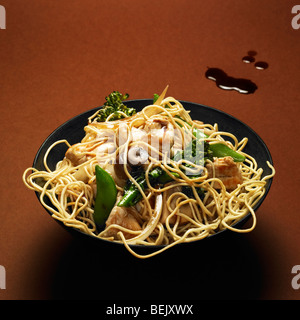 Chinese chicken noodles with mushrooms, mange tout and broccoli sprouts - Stock Photo