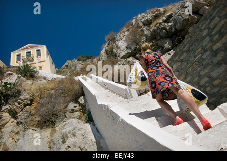 A woman with two bags of heavy shopping climbs steep steps to a house on the Greek island of Symi