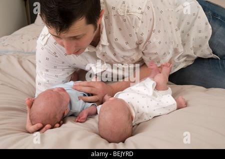 Parent comforting crying babies, twin boys - Stock Photo