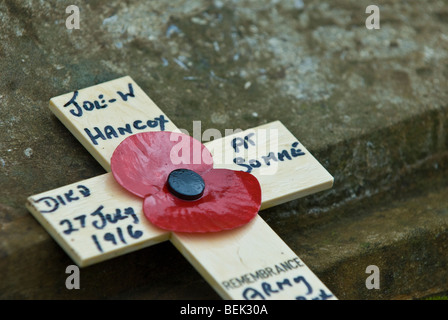 A single wooden cross and poppy at the base of a memorial on armistice day which is an annual event in the UK. - Stock Photo