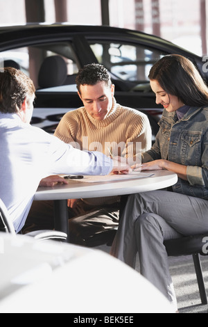 Young woman signing a document with a mid adult man sitting beside her in front of a car salesman - Stock Photo