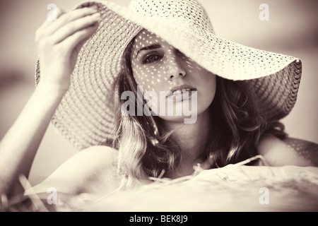 Young woman in a hat portrait. Soft yellow tint. - Stock Photo