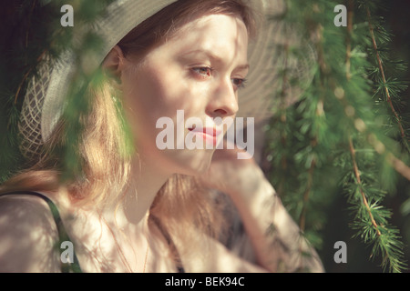 Young woman portrait in a park. Soft colors. - Stock Photo