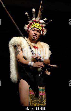 Warrior from the Orang Ulu Tribe in Feathered Head-dress & Animal Skins with Blowpipe Dance Sarawak Malaysia Borneo - Stock Photo
