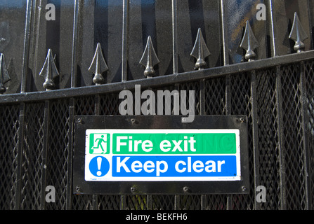 fire exit sign and keep clear sign fixed to a cast iron gate with arrowhead decoration, in queensway, london, england - Stock Photo