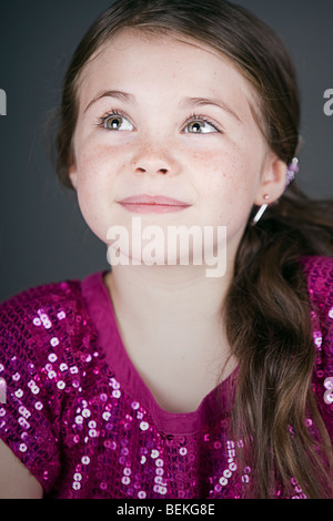 Shot of a Cute Brown Haired Girl Looking Up Off Camera - Stock Photo