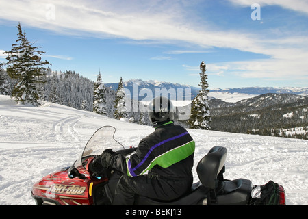 Snowmobile rider pauses to admire scenery on the way to Two Top Mountain in Gallatin National Forest, outside Yellowstone - Stock Photo