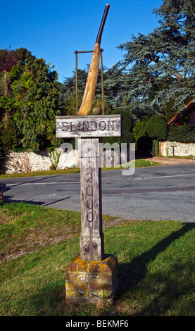 A village sign with a wooden carved cricket bat and ball leaning against a wicket Slindon, West Sussex, England, - Stock Photo