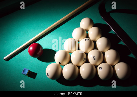 Pool balls on light beam. Balls pyramid with cue on a pool table. - Stock Photo