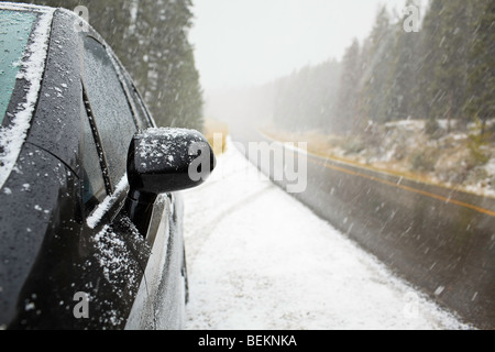 Parked car on side of highway during winter storm, Bow Valley Parkway, Banff National Park, Alberta, Canada. - Stock Photo