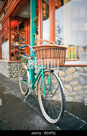 Cruiser bicycle with basket parked outside a storefront, Banff, Alberta, Canada. - Stock Photo