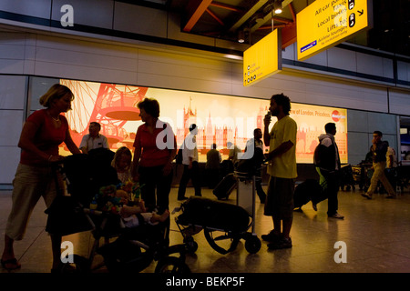 Half-silhouetted figures add to the bustle of a hectic arrivals concourse at Heathrow Airport's Terminal 5. - Stock Photo