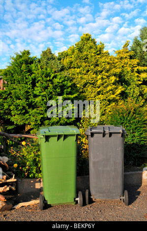 A green and black / grey  wheelie bin sit side by side on the driveway  of a house. - Stock Photo