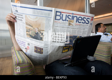 A Business class passenger hides his face while reading the Business section of the Daily Telegraph in BA's Terminal - Stock Photo