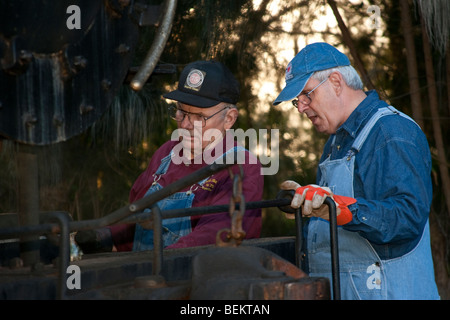 Two engineers working on a 1930s steam locomotive in Florida - Stock Photo