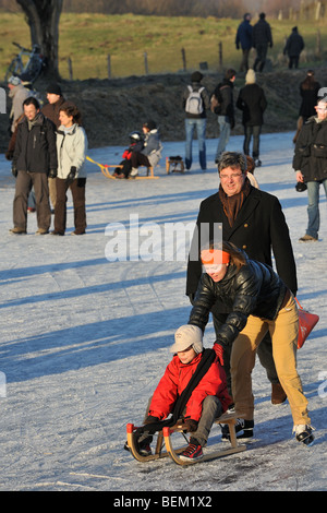 Child on sledge pushed by mother and walkers walking on ice of frozen river in winter - Stock Photo