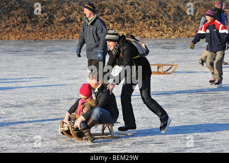 Mother and son on sledge pushed by father and ice skaters skating on frozen river in winter - Stock Photo