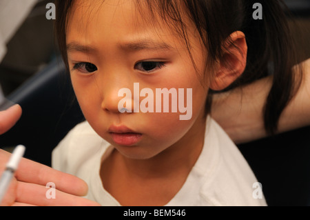 A 5-year-old girl is vaccinated for the 2009 H1N1 influenza, also known as the Swine Flu, with an intranasal vaccine. - Stock Photo