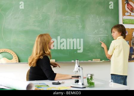 Boy solving math problem on blackboard, looking at teacher - Stock Photo