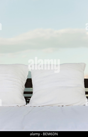 Pillows on bed, clouds in background - Stock Photo