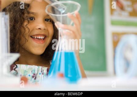 Little girl transferring liquid from test tube to beaker - Stock Photo