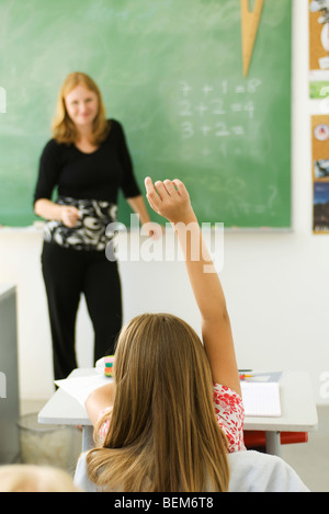 Girl in classroom raising hand to answer question - Stock Photo