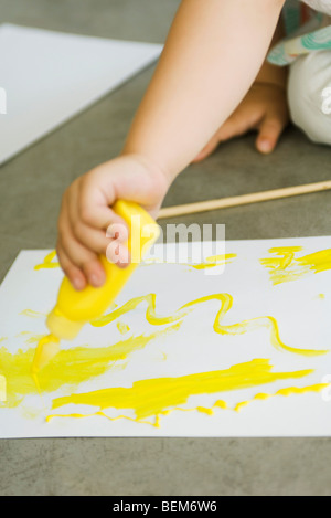 Child squeezing paint onto paper, cropped - Stock Photo