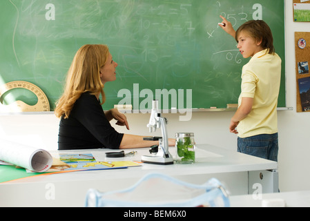 Boy solving math problem on blackboard, looking at teacher for assistance - Stock Photo