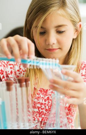 Girl transferring liquid from test tube to beaker - Stock Photo
