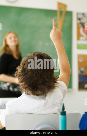 Elementary student raising hand in class, rear view - Stock Photo