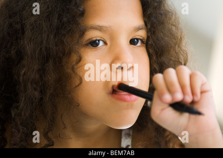 Little girl holding pen against mouth, looking away - Stock Photo