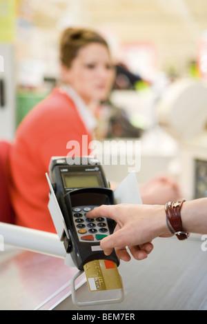 Customer entering pin into credit card reader keypad - Stock Photo
